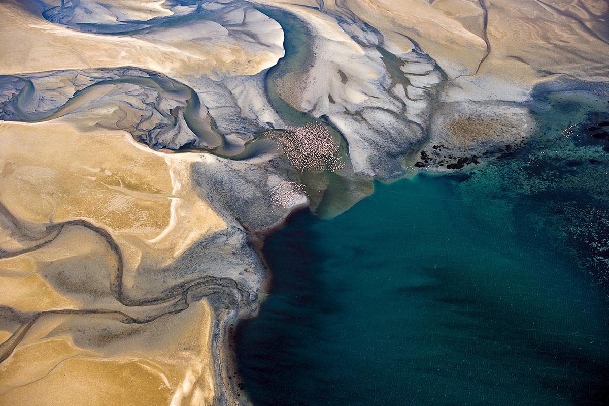 Flamingoschwarm über der Lagune von Sandwich Harbour an der Küste Namibias.