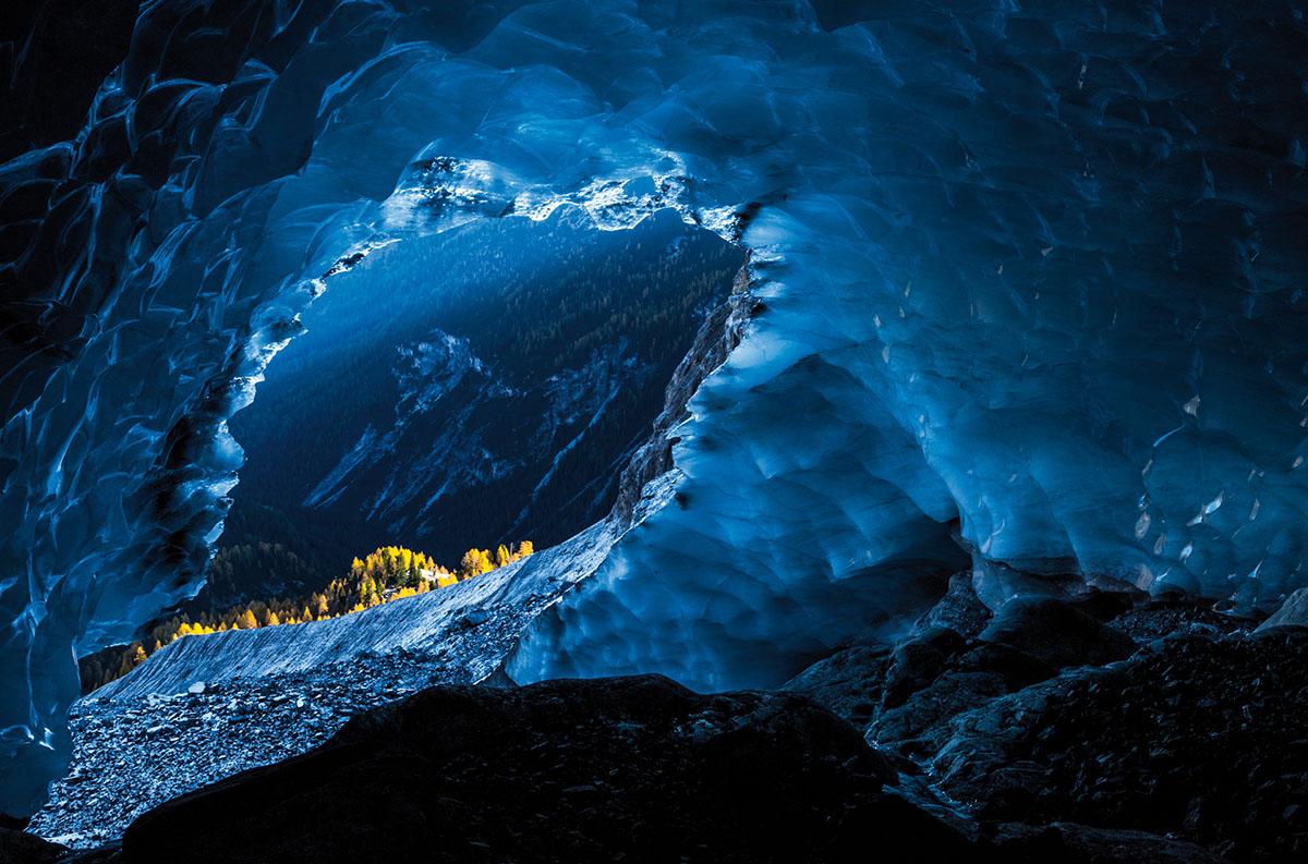 Gesamtsieger und Kategoriesieger Landschaft. »Die letzte Gletscherhöhle der Ortler-Alpen«. Viele Male hatte ich diese wunderschöne Gletscherhöhle in den Ortler-Alpen bereits besucht. Ein echtes Meisterwerk der Natur. Wegen der Gletscherspalte reduziert sich die Größe der Höhle kontinuierlich und wird in ein paar Jahren komplett verschwunden sein. Im Hintergrund sind Lärchen zu sehen, die vom ersten Tageslicht beleuchtet werden.