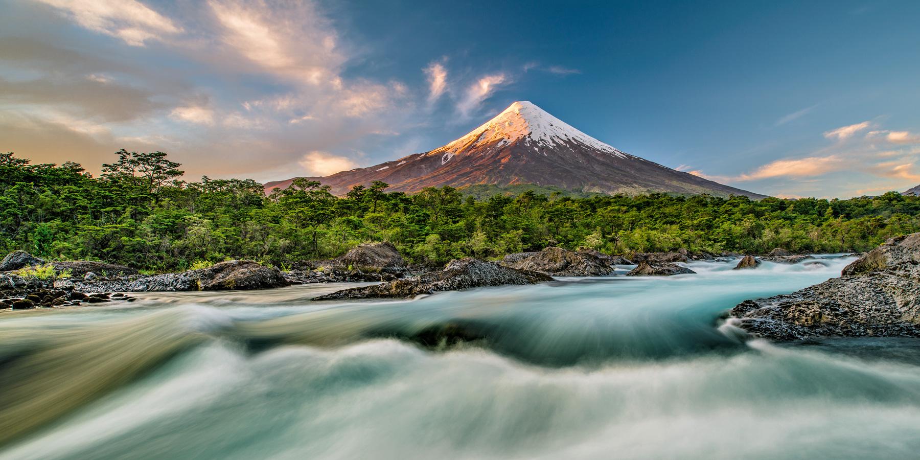 """Der nahezu perfekt konische Vulkan Osorno im Vicente Pérez Rosales-Nationalpark zusammen mit den Stromschnellen  """"Saltos del Petrohué"""", die sich durch eine beeindruckende Basaltlandschaft ergießen."""